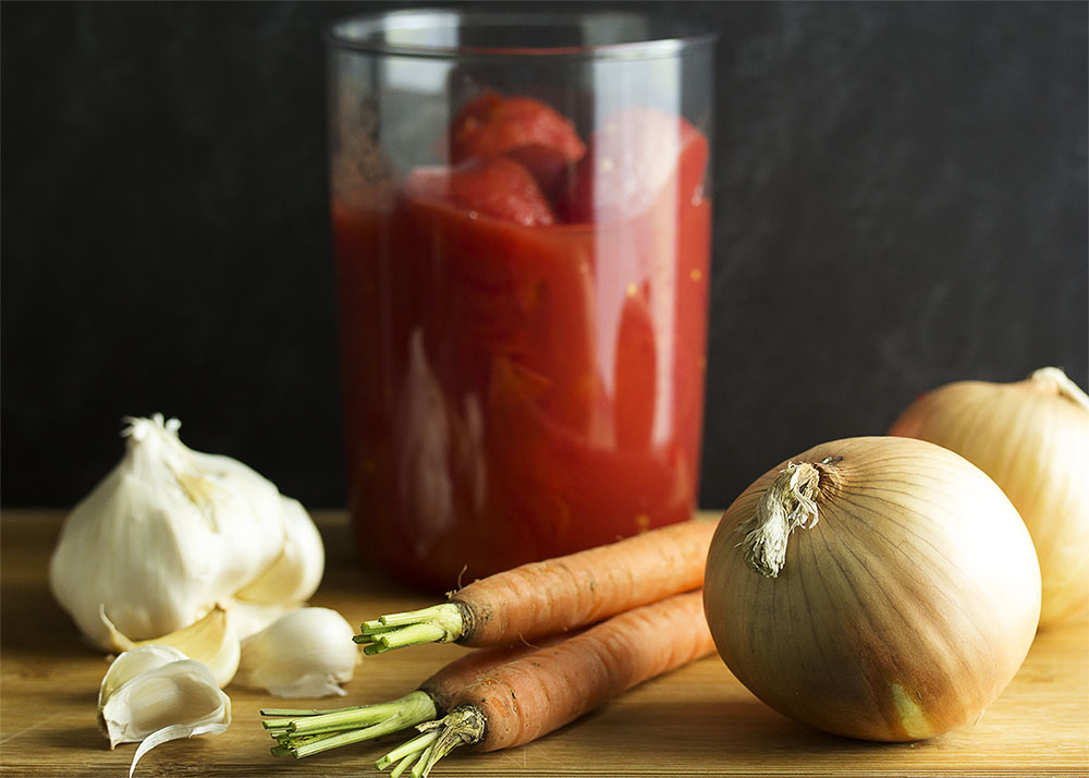 Ingredients for Italian marinara sauce - garlic, onions, carrots, and canned whole tomatoes.