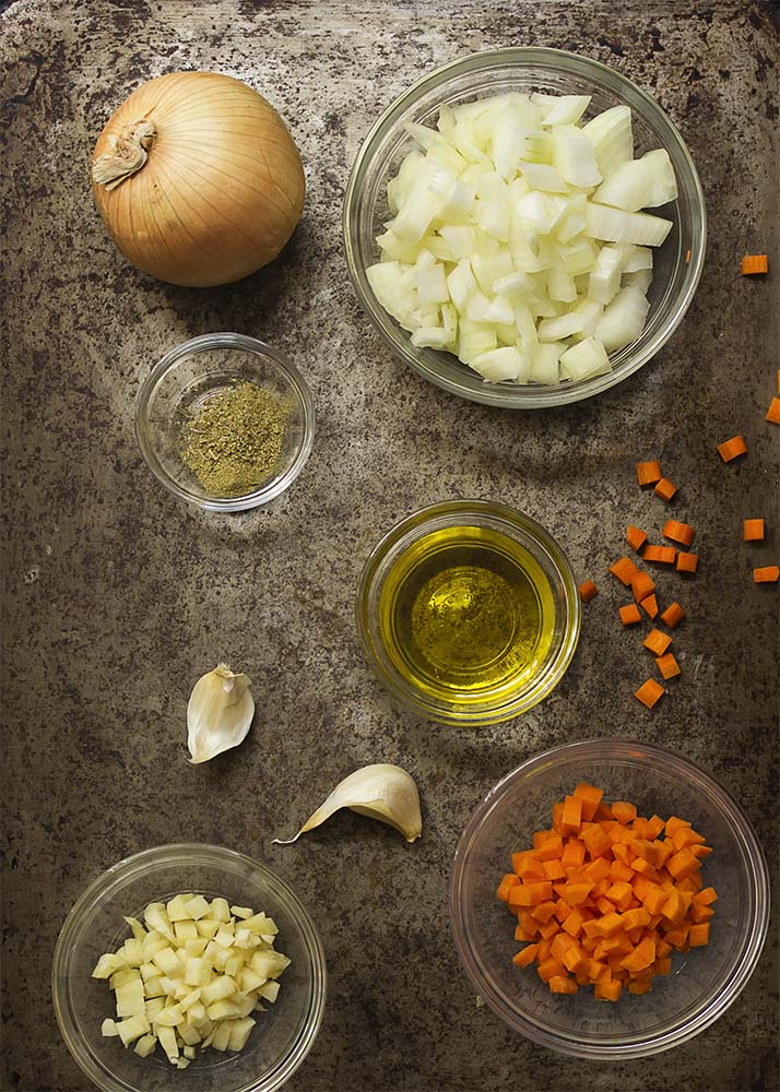 Top down view of chopped onions, garlic, and carrots along with measured bowls of olive oil and dried herbs.
