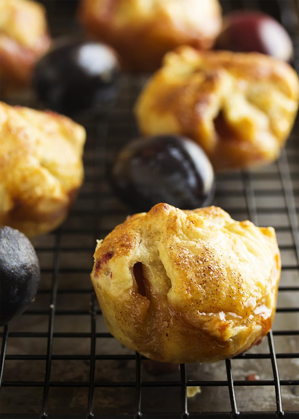 Pull out your muffin tin for easy clean up and wrap plum slices and spiced honey in puff pastry to make these puff pastry plum tarts. Bake until they are puffed and golden, then drizzle with a little more spiced honey, and serve with mascarpone whipped cream. | justalittlebitofbacon.com
