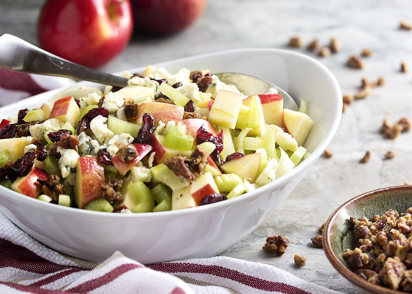 Maple glazed pecans, blue cheese, and diced apples combine with dried cranberries and sliced celery in this fall harvest salad. Great for weeknight dinners and a wonderful side for Thanksgiving.   justalittlebitofbacon.com