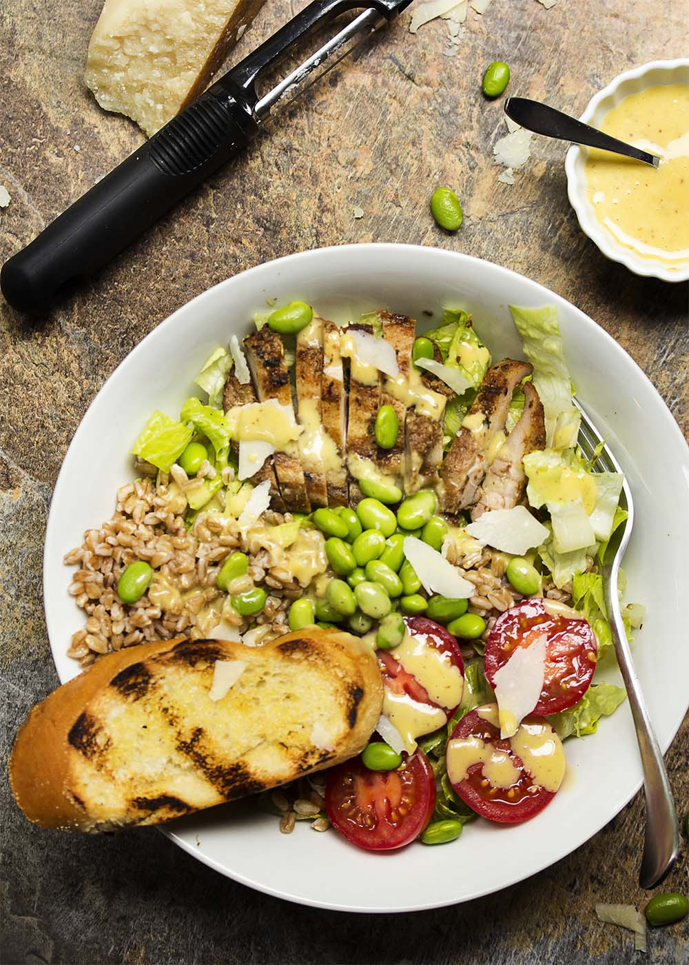 Caesar salad becomes satisfying meal in a bowl with the addition of spicy grilled chicken thighs, farro, tomatoes, and edamame. | justalittlebitofbacon.com