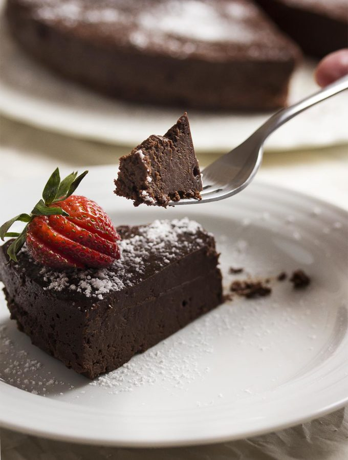 This easy flourless chocolate cake is amazingly dense, rich and decadent. Every bite is packed with intense bittersweet chocolate flavor. | justalittlebitofbacon.com