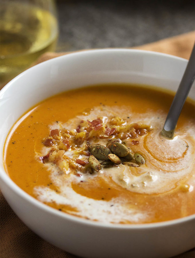 This creamy, spicy roast pumpkin soup is full of Spanish flavors like paprika and roasted red peppers and topped with crispy pancetta. | justalittlebitofbacon.com