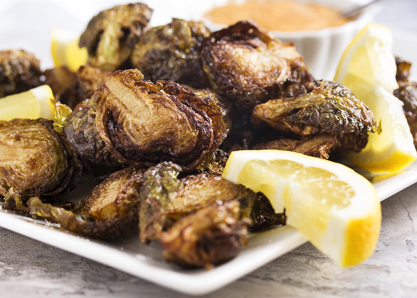 Golden brown and crispy deep fried brussels sprouts on a platter with lemon slices and maple aioli.
