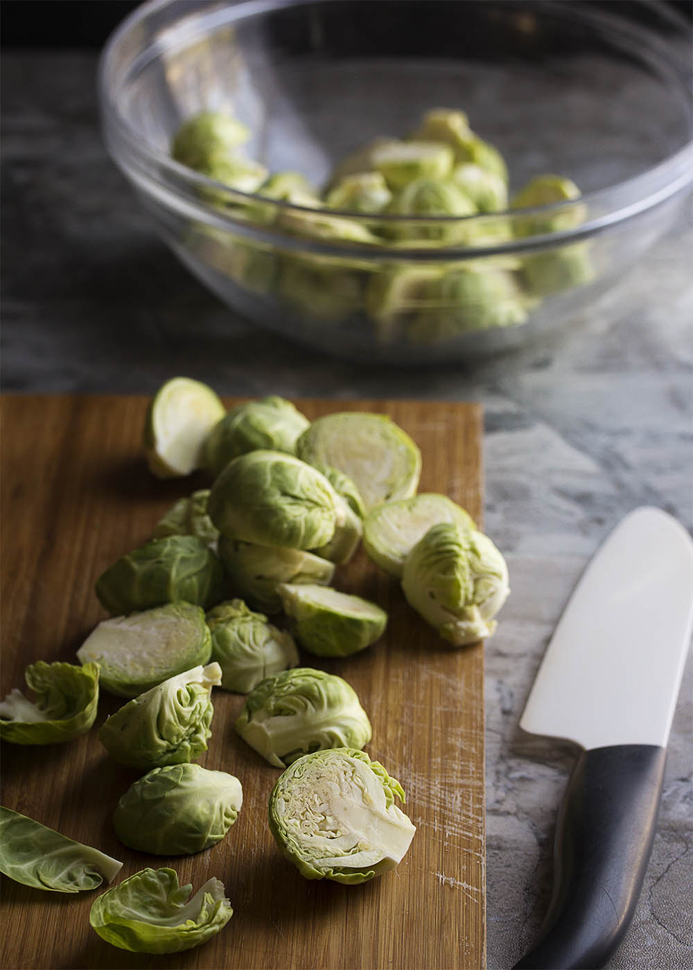 Sliced and trimmed Brussels sprouts on a cutting board ready to be fried.