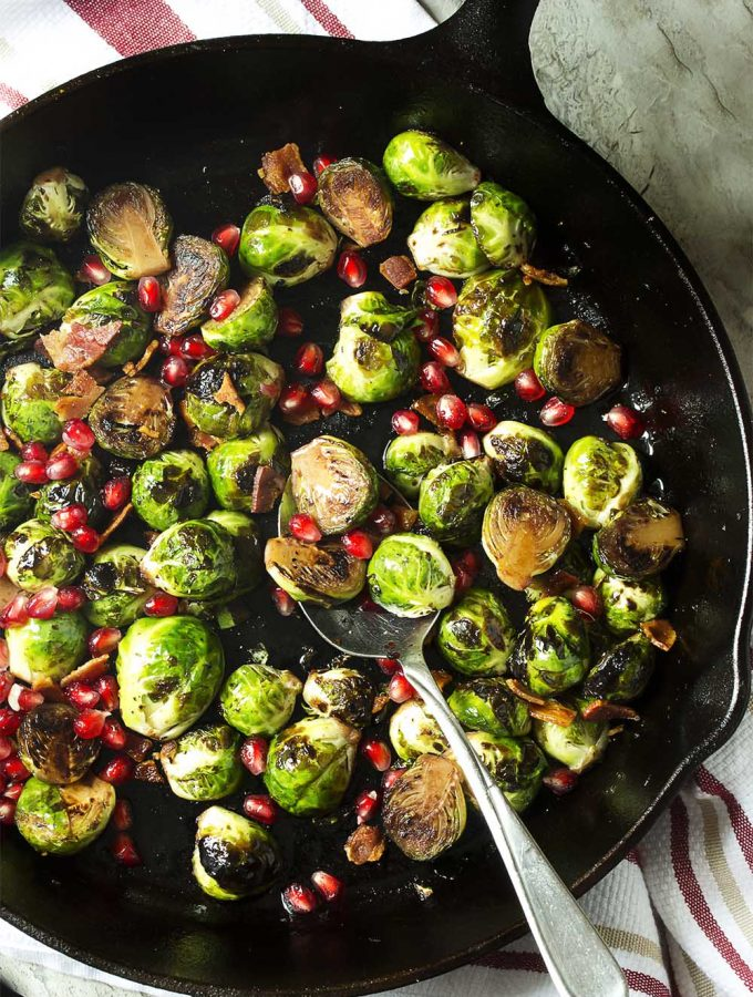 This yummy winter and holiday side dish features pan roasted brussels sprouts, crispy bacon, and sweet pomegranate seeds. Great for Thanksgiving and Christmas or as an easy, weeknight side. | justalittlebitofbacon.com