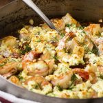 Juicy, plump shrimp are flambeed in brandy then topped with feta before being broiled over a bed of tomatoes in this classic Greek dish! | justalittlebitofbacon.com