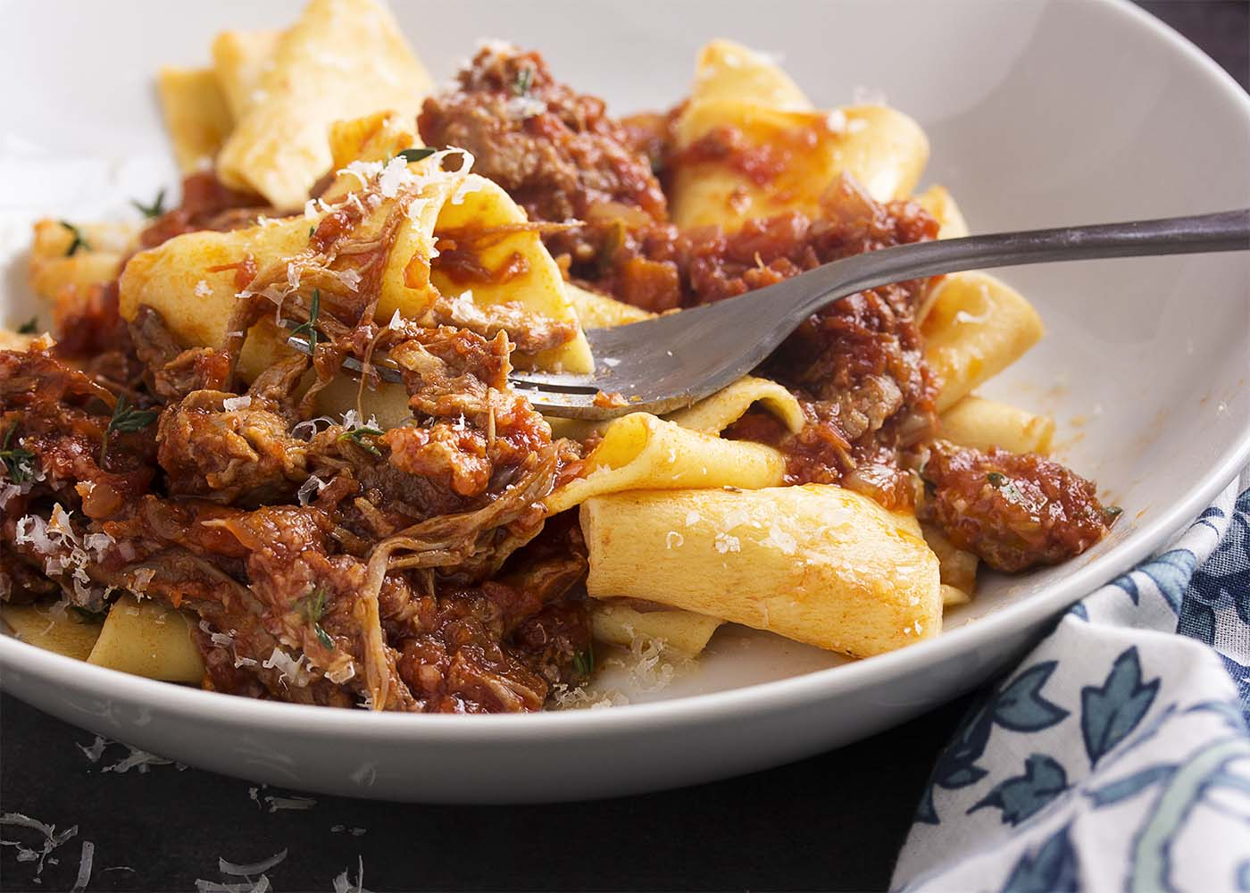 A fork digging into a bowl of pappardelle tossed with pork ragu.