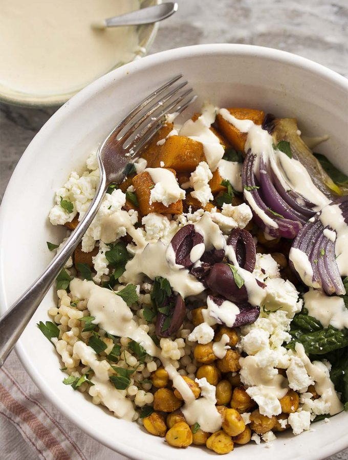 Turn Greek salad into a satisfying one bowl dinner with this Greek Buddha Bowl! It's full of chickpeas, roasted squash, pearl couscous, feta, and olives all over a bed of spinach and drizzled with a yogurt, tahini dressing.   justalittlebitofbacon.com