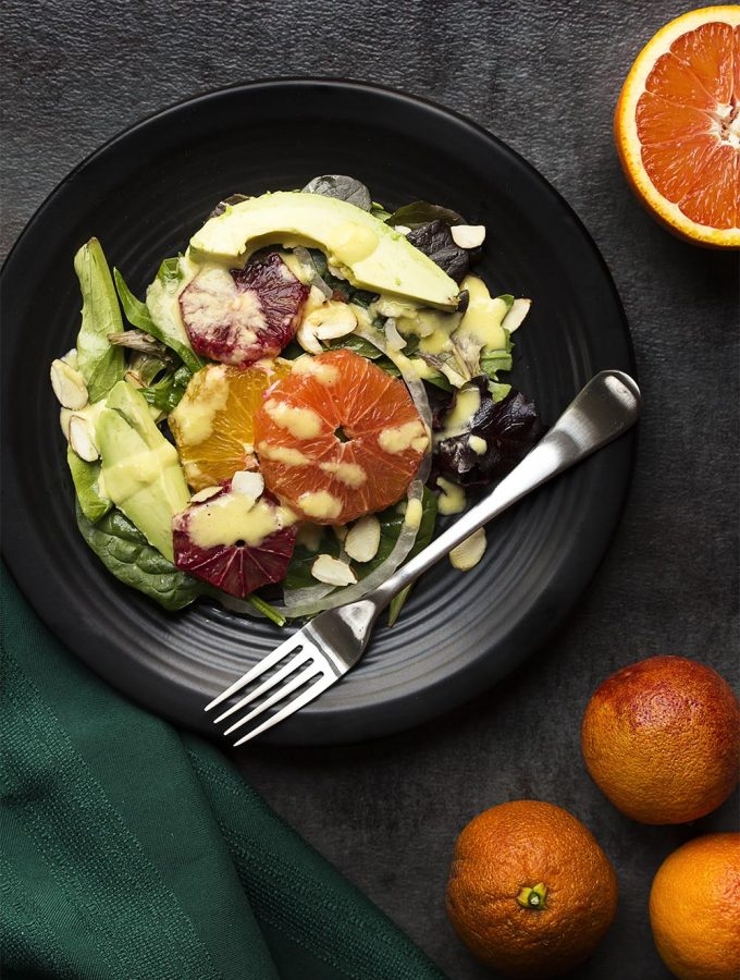 Blood oranges are layered with cara cara oranges and navel oranges over mixed greens in this vibrant and healthy winter citrus salad. | justalittlebitofbacon.com