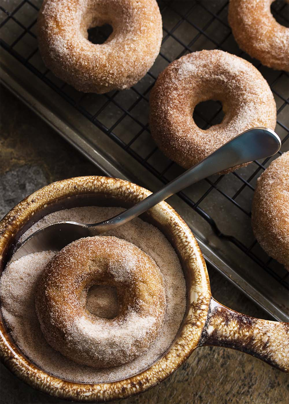 Churros just got a little bit healthier! No deep frying needed. Baked churro donuts are make in a donut pan and rolled in cinnamon sugar. This means you can totally justify the spicy chocolate sauce to dip them in. | justalittlebitofbacon.com