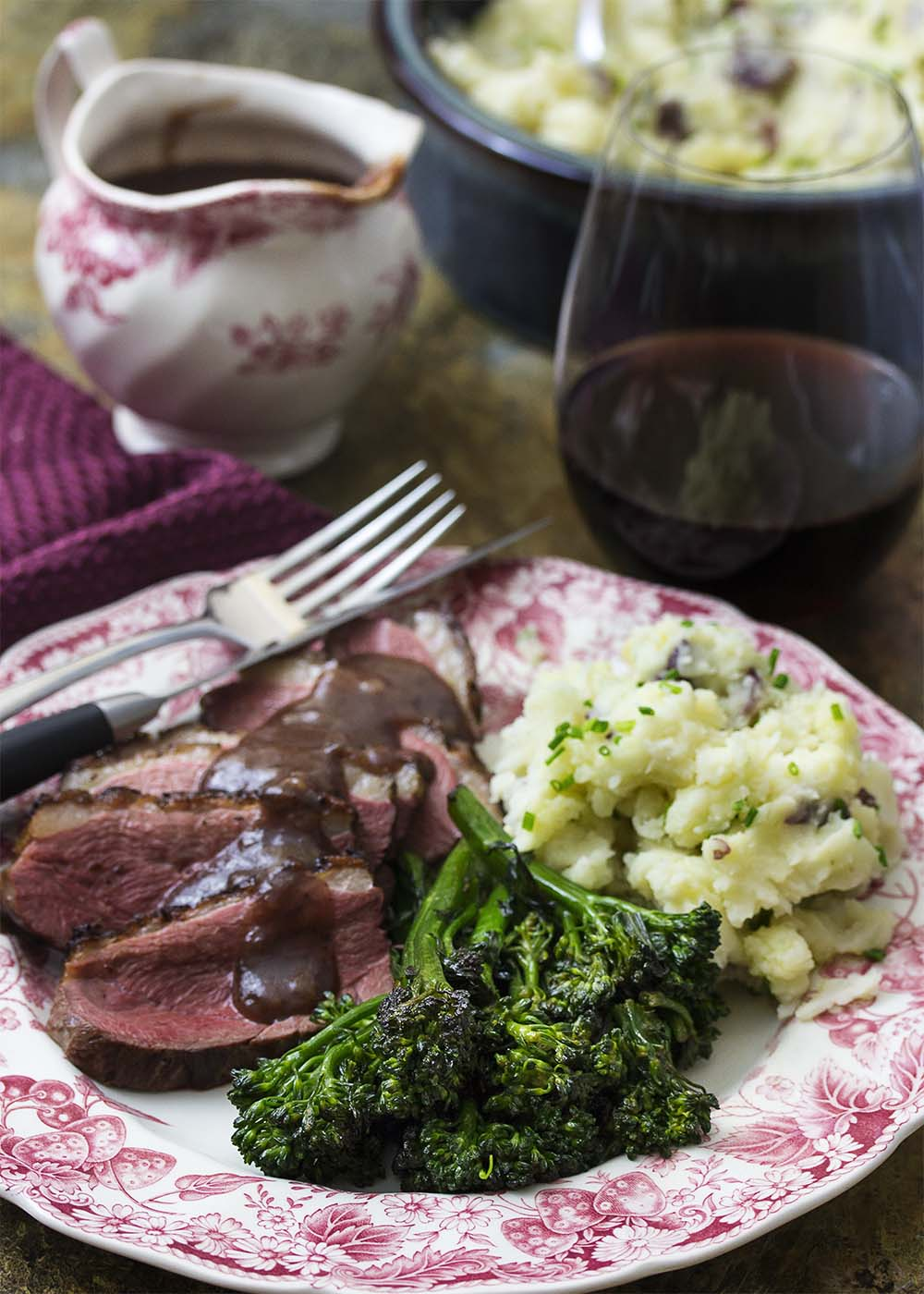 Crispy, seared duck breast is paired with a sweet and spicy port cherry sauce and tender broccolini sauteed in the duck fat for this romantic dinner menu. | justalittlebitofbacon.com