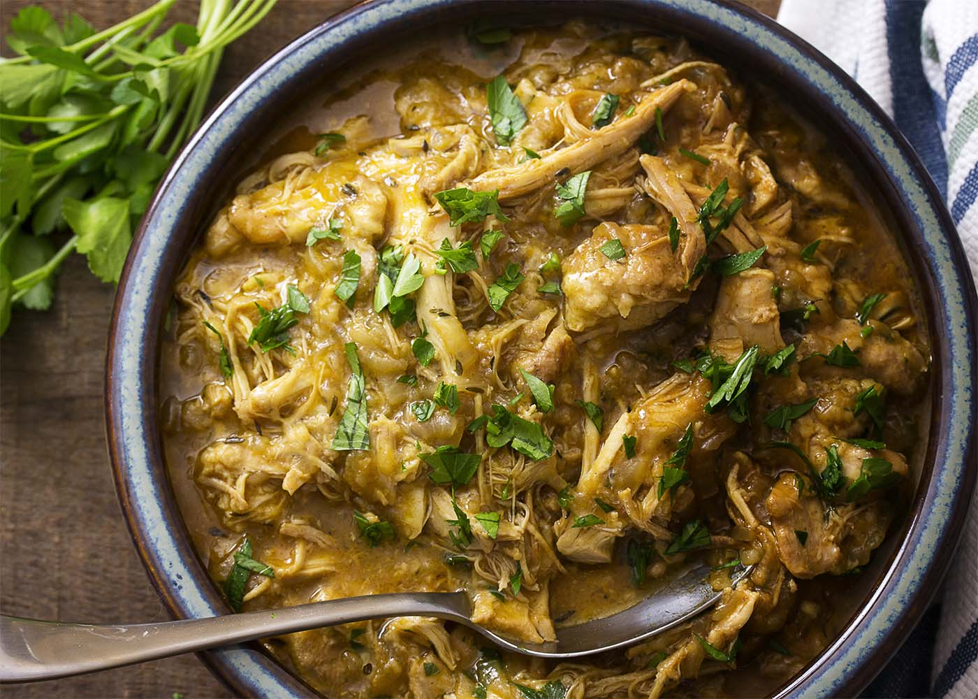 Turn on the slow cooker and come home to this recipe of chicken thighs cooked into a comforting stew with a rich, onion and cheese gravy. Great served over roasted winter squash or mashed potatoes! And wonderful for sandwiches the next day. | justalittlebitofbacon.com