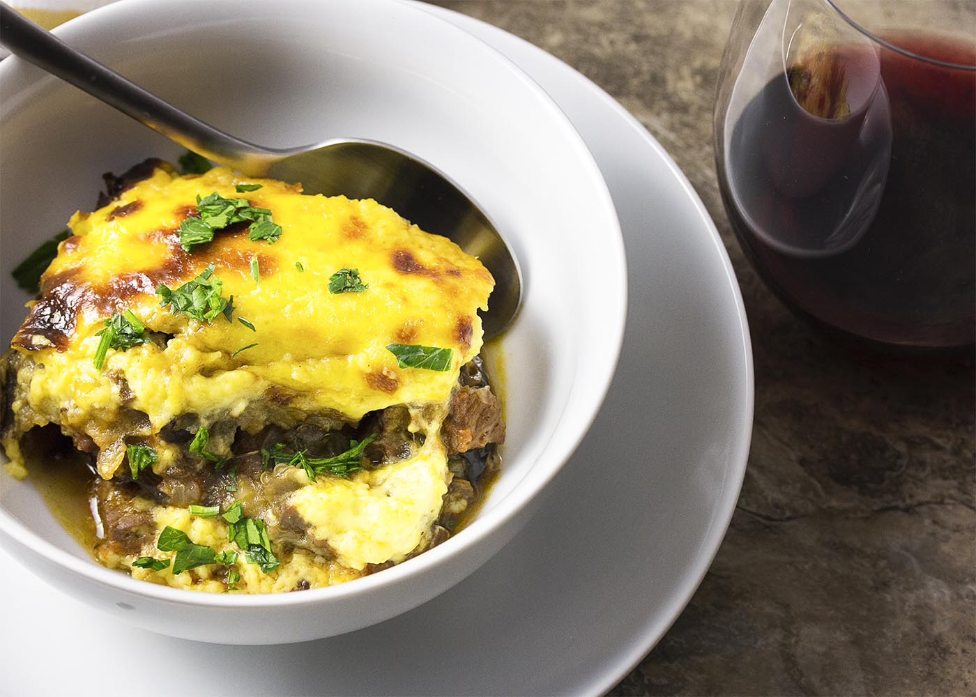 Greek comfort food at its best! Layers of eggplant and lamb are covered with creamy bechamel sauce and then baked until bubbly and golden in this leftover lamb moussaka. | justalittlebitofbacon.com