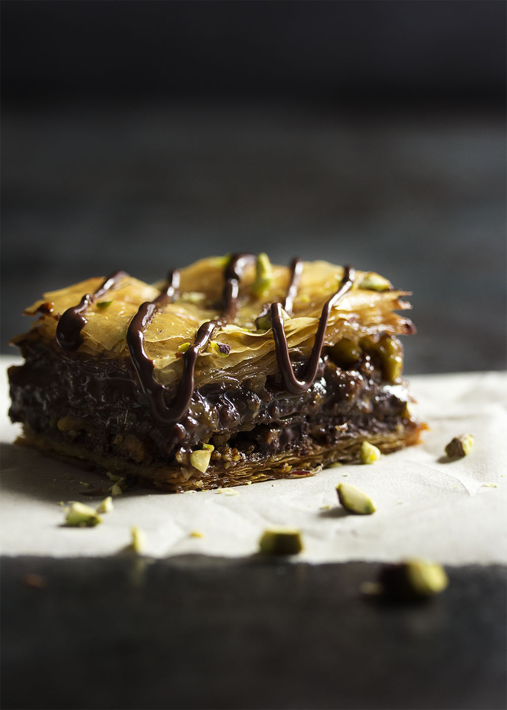 This chocolate baklava is packed full of pistachios and bittersweet chocolate, then drizzled with a honey syrup to make wonderfully rich Greek dessert! | justalittlebitofbacon.com