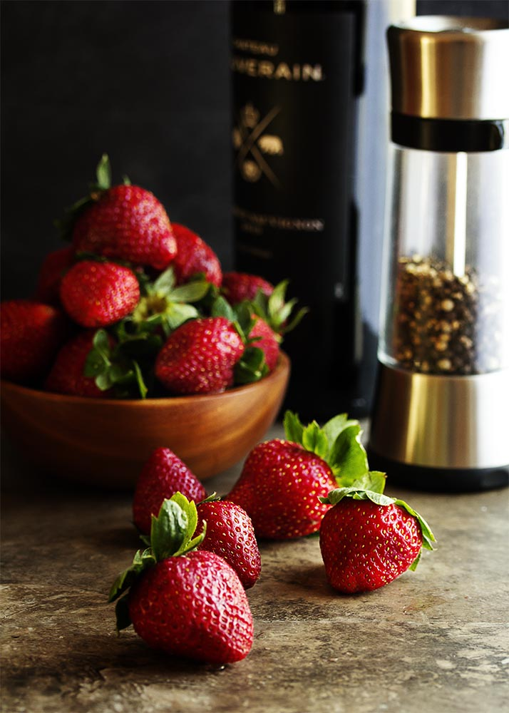 Strawberry sauce with a twist! Fresh strawberries are simmered in wine and spiced with black pepper for an intense and complex flavor. Great on shortcake, cheesecake, ice cream, pancakes, waffles and more! | justalittlebitofbacon.com