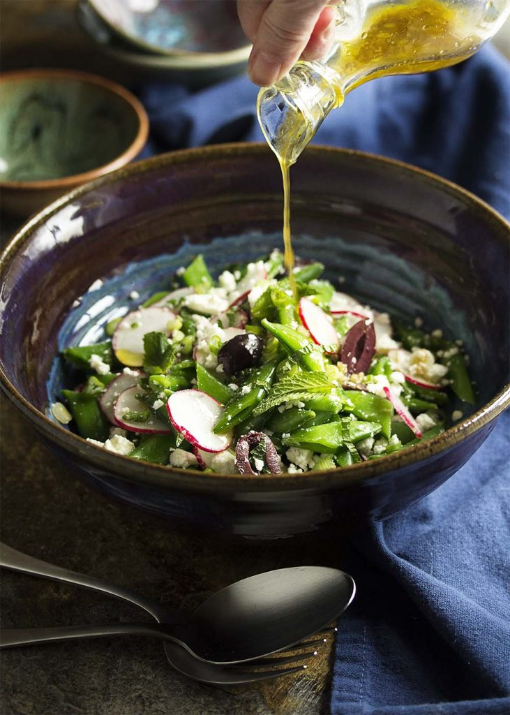 Celebrate spring with sweet snap peas and spicy radishes all tossed with feta, kalamata olives, and scallions in this Greek snap pea salad.   justalittlebitofbacon.com