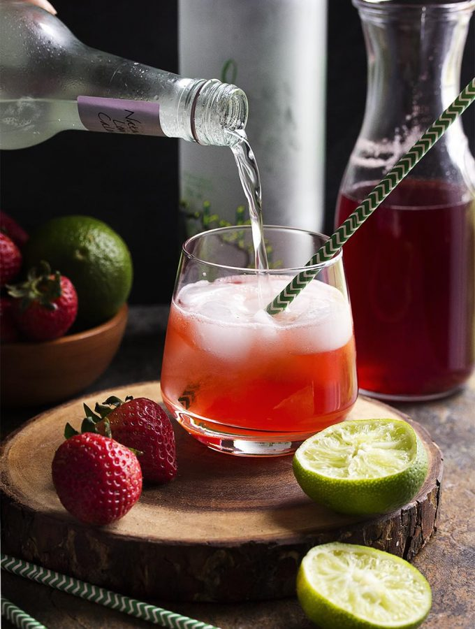 Homemade strawberry syrup topped with ginger beer makes this Brazilian strawberry caipirinha cocktail a refreshingly fruity fizzy drink perfect for summer! | justalittlebitofbacon.com