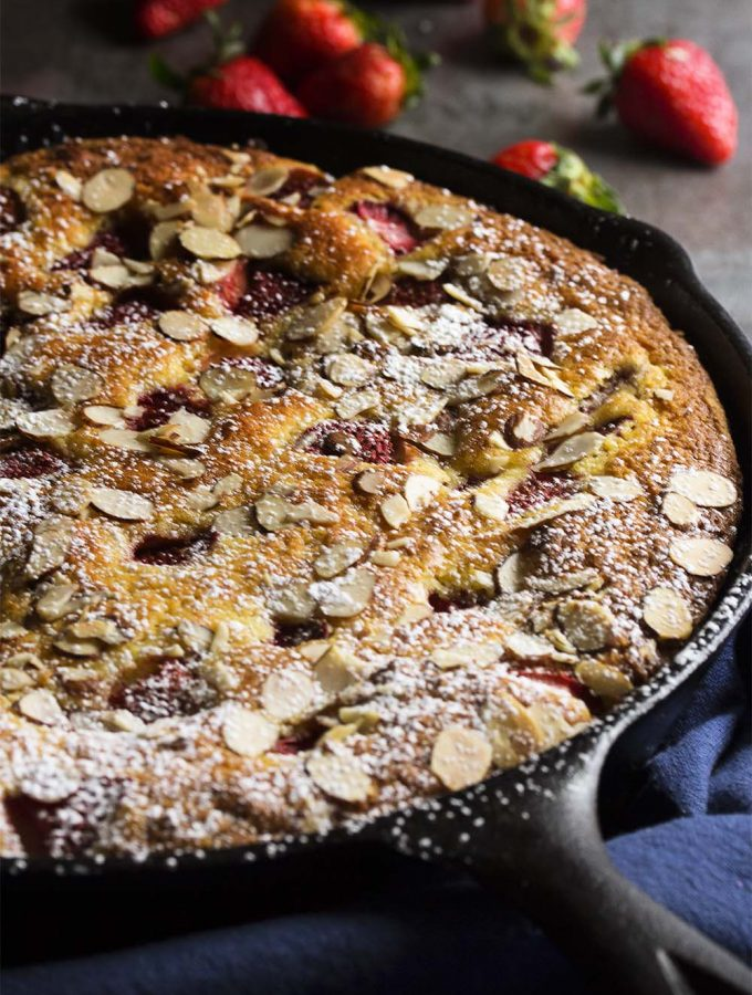 This easy strawberry yogurt cake is topped with sliced almonds and cooks right in your cast iron skillet! It's great as a breakfast cake or for an evening dessert with some vanilla ice cream. | justalittlebitofbacon.com