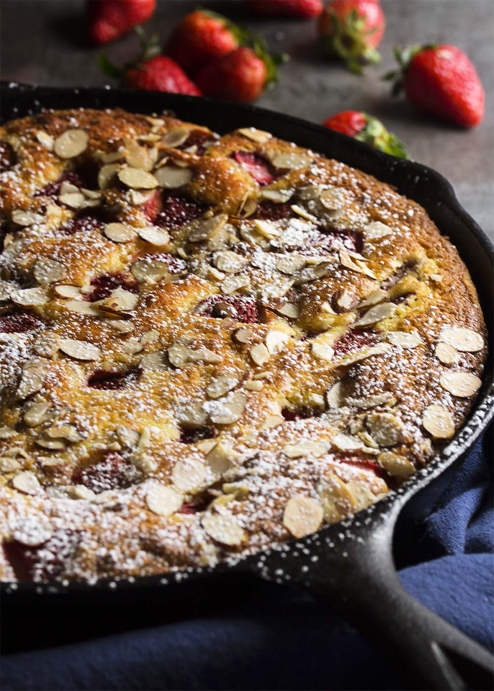 Strawberry yogurt skillet cake baked in a cast iron skillet topped with sliced almonds and powdered sugar.