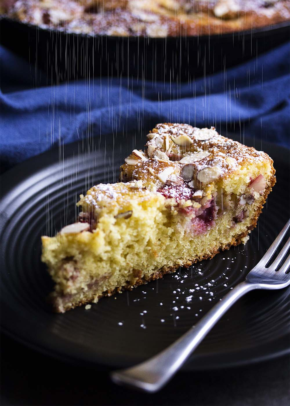This easy strawberry yogurt cake is topped with sliced almonds and cooks right in your cast iron skillet! It's great as a breakfast cake or for an evening dessert with some vanilla ice cream.   justalittlebitofbacon.com