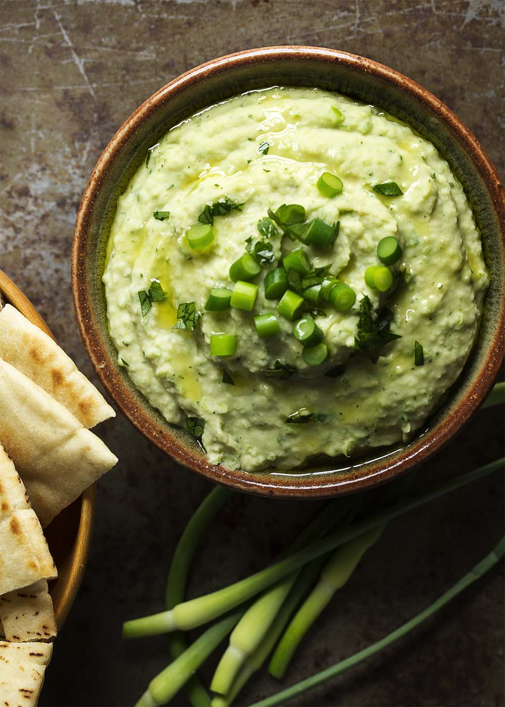 Wondering what to do with garlic scapes? Puree them into a quick and creamy, garlicky bean and garlic scape dip! Great as a healthy snack or for a party! | justalittlebitofbacon.com