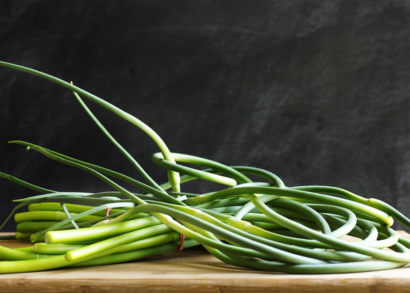 What are garlic scapes? How to use garlic scapes? How to cut and store garlic scapes? These questions and more answered in this ingredient spotlight. | justalittlebitofbacon.com