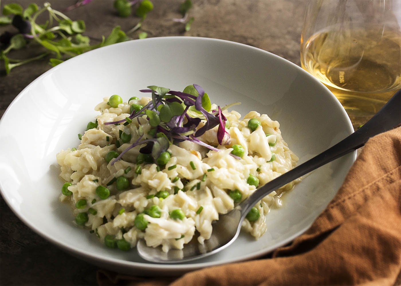 Creamy crab risotto makes a great one-pot meal! Sweet crab meat is mixed with mascarpone and baby peas in this quick dinner. Great for a weeknight or for date night.   justalittlebitofbacon.com