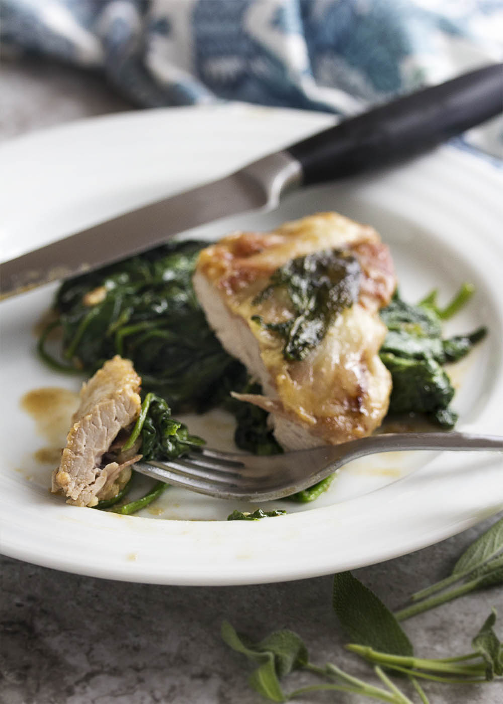 This pork saltimbocca will jump in your mouth! Pork tenderloin topped with prosciutto, fontina, and sage makes a tender and quick cooking meal. Finish off the recipe with a white wine pan sauce and serve with sauteed spinach. | justalittlebitofbacon.com
