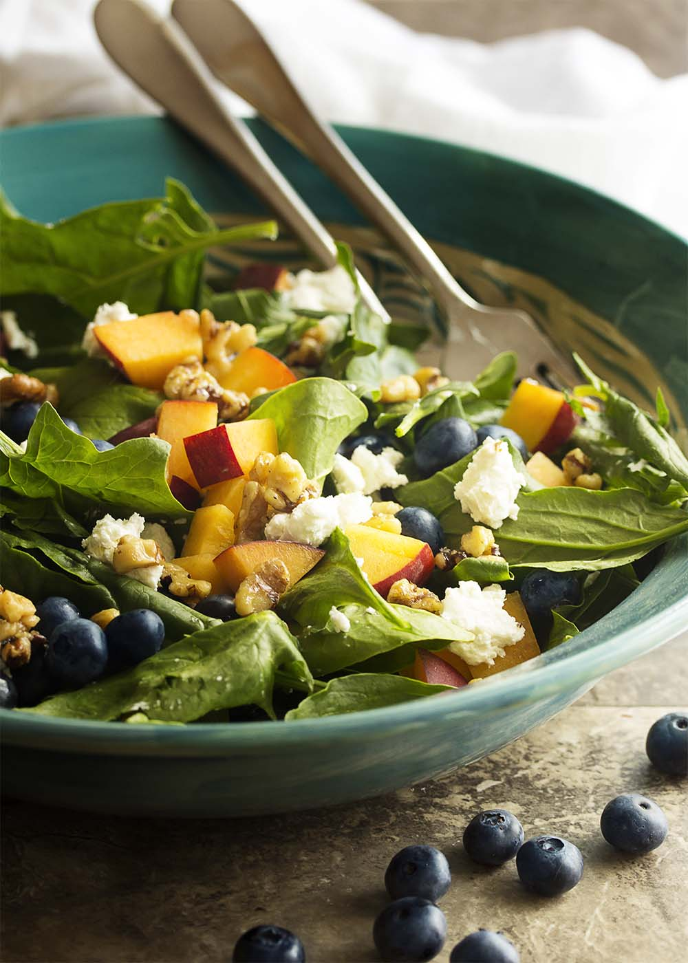 Punch up your spinach salad with seasonal summer fruits, creamy cheese, and glazed walnuts in this peach and blueberry spinach salad. | justalittlebitofbacon.com
