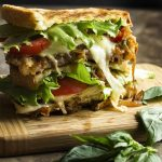 Creamy fontina cheese and sweet caramelized onions are paired with sliced chicken and a basil aioli in this chicken pesto panini.   justalittlebitofbacon.com