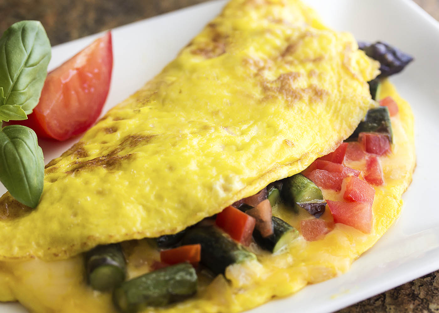 Take advantage of fresh asparagus to make a healthy spring omelette! This asparagus omelette is full of smoked gouda cheese, sauteed onions, and tomatoes. Great for breakfast, brunch, or even dinner. | justalittlebitofbacon.com