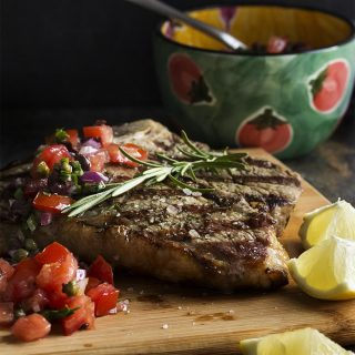 Grilled Tuscan steak is a simple, yet elegant Florentine style specialty! Start with a couple of thick-cut, bone-in steaks, add fresh herbs and a hot grill, then finish them off with fruity olive oil and a squeeze of lemon. | justalittlebitofbacon.com