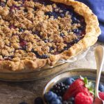 What to do with the bounty of strawberries, blueberries, raspberries and blackberries available in the summer? Make a one crust mixed berry pie with a crunchy and sweet crumble topping! | justalittlebitofbacon.com