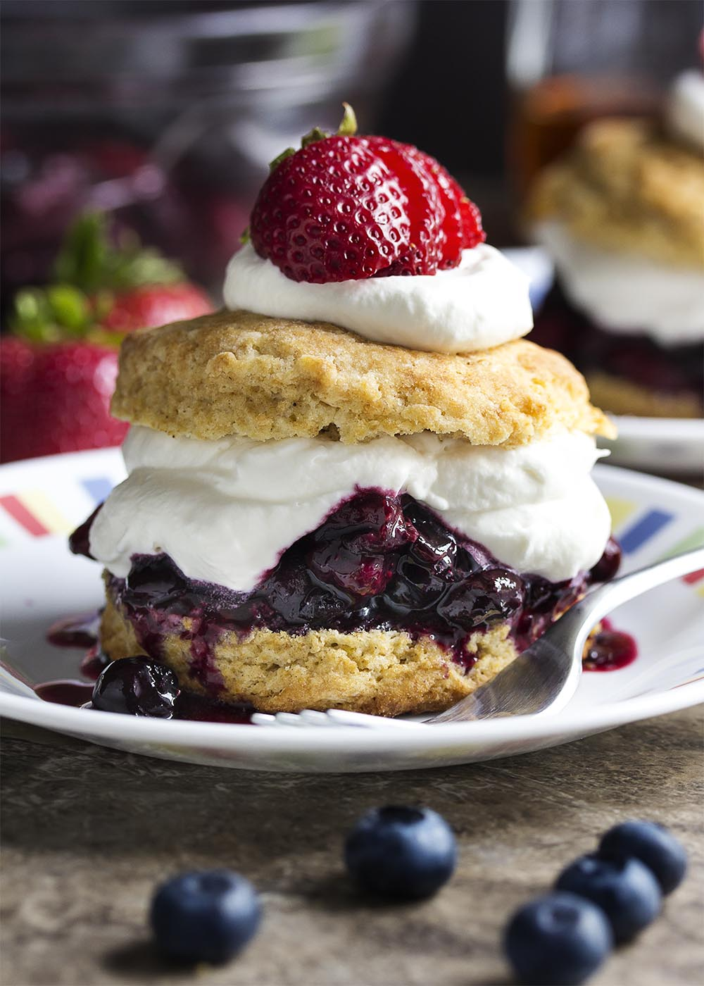 Strawberry shortcake gets a sophisticated makeover! Just in time for summer. Intensely flavored roasted strawberries and blueberries are spooned onto cinnamon spiced biscuits and topped with bourbon whipped cream in this berry shortcake. | justalittlebitofbacon.com