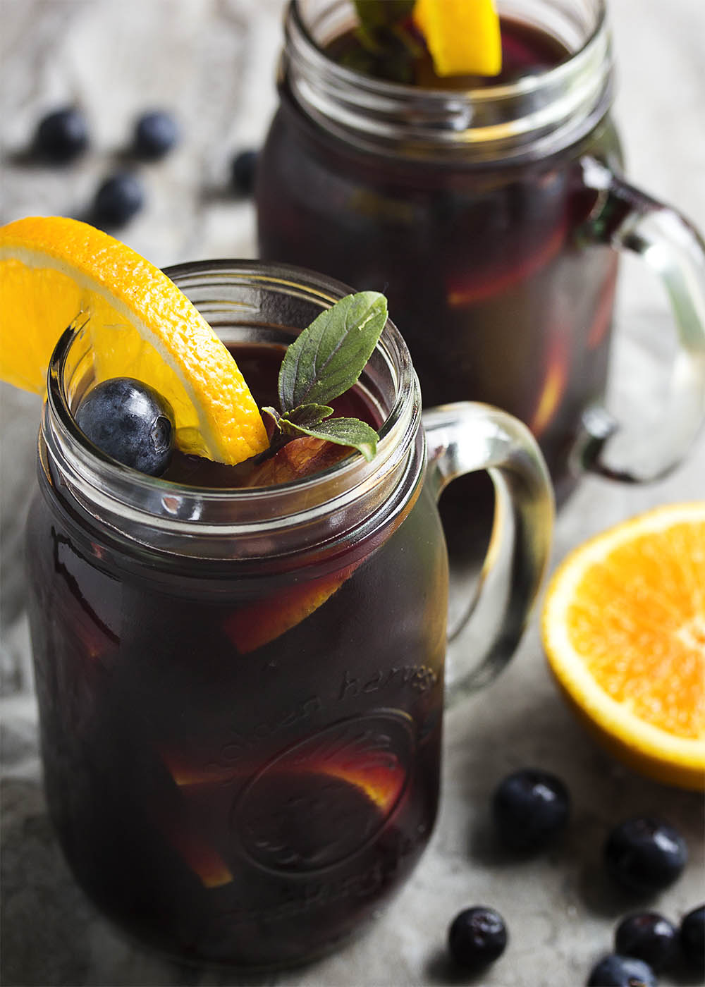 This easy orange and blueberry sangria is a great way to enjoy red wine on a hot day! It's not too sweet and bursting with summer fruit. Perfect for sipping outdoors. | justalittlebitofbacon.com