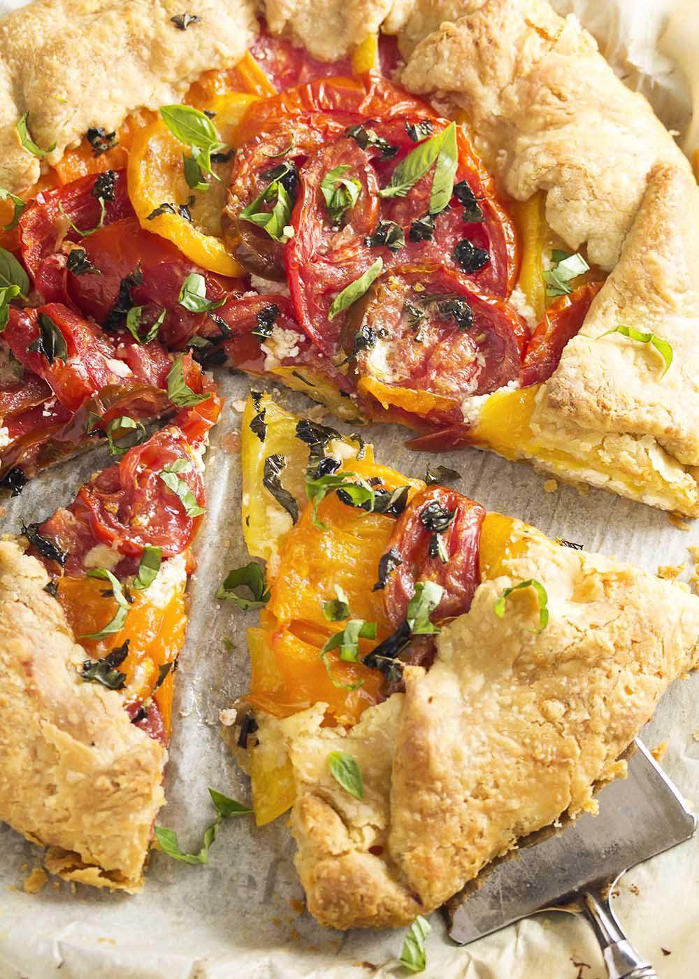 This savory tomato galette is a rustic tart in the French tradition, full of juicy, sweet heirloom tomatoes and creamy goat cheese and then folded into a simple pastry crust. | justalittlebitofbacon.com