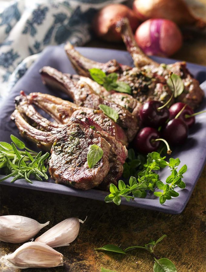 Lamb rib chops are coated with a thyme, rosemary, and garlic marinade then grilled to medium rare and topped with a cherry port sauce in this elegant summer dinner.