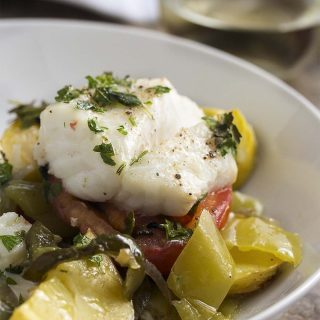 Baked Mediterranean cod is a one dish meal that's big on flavor and easy on cleanup! Thick cut cod is flavored with olive oil and fresh herbs and baked over a bed of mixed vegetables in this simple oven dinner. | justalittlebitofbacon.com