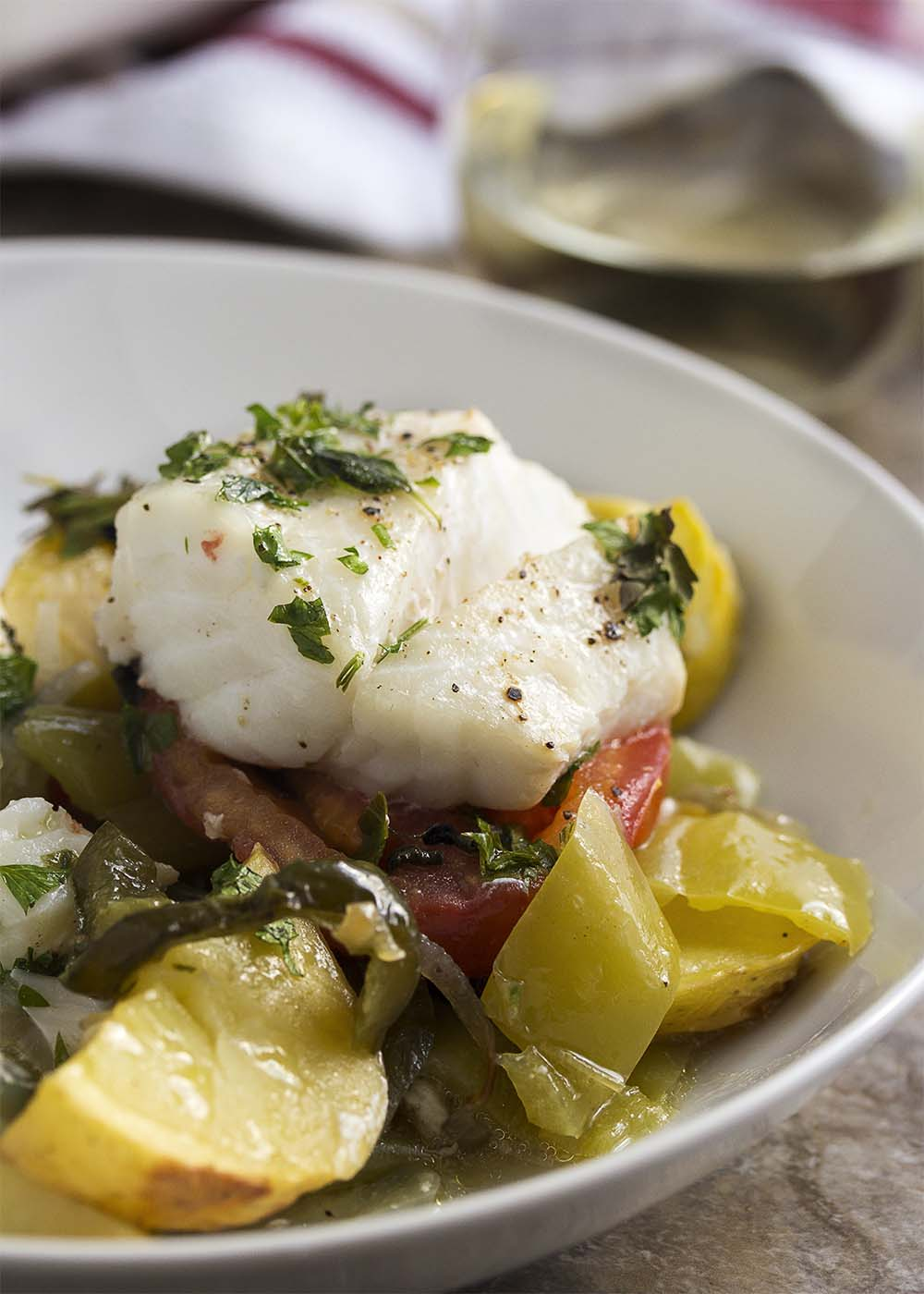 Close up of a piece of baked cod with Mediterranean vegetables underneath.