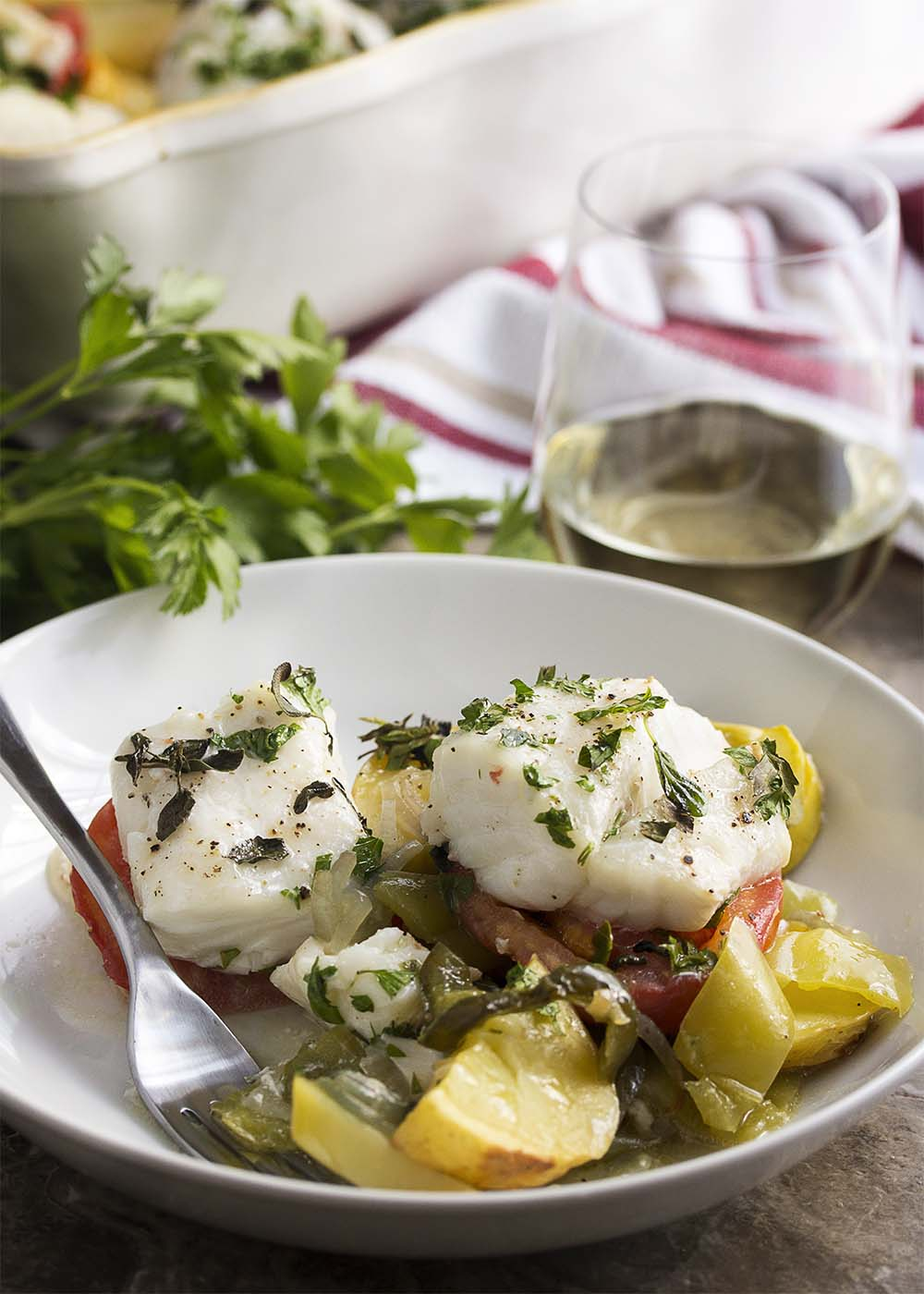 A shallow bowl filled with baked Mediterranean cod with mixed vegetables. A fork in the bowl and a glass of wine in the background.
