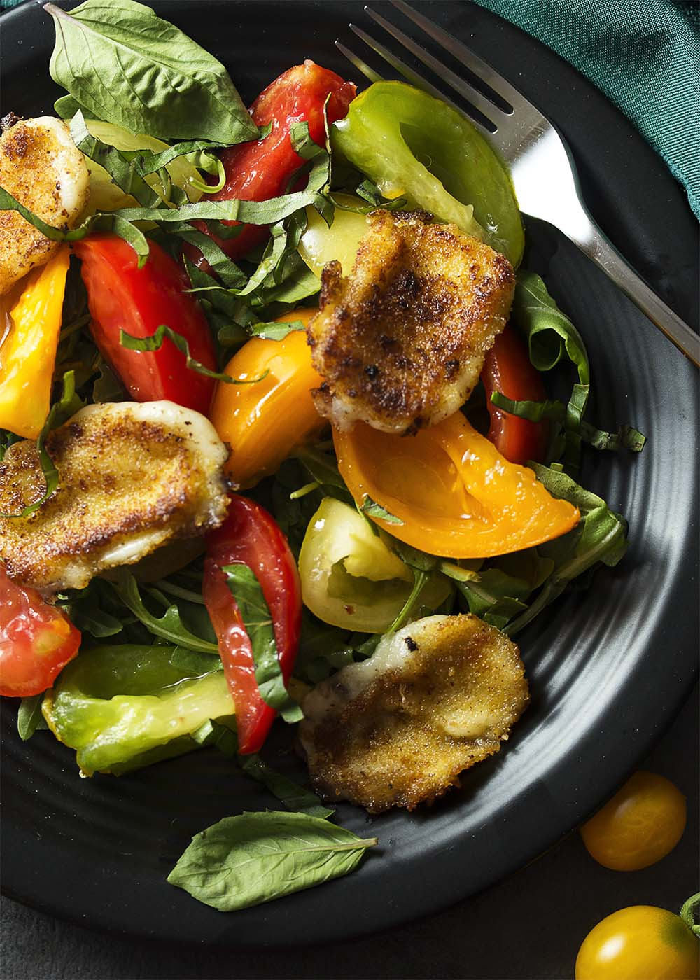 My tomato arugula salad is lightly tossed with a simple vinaigrette and topped with fried mozzarella slices which have been dredged in breadcrumbs and pan fried until golden brown and crispy. | justalittlebitofbacon.com