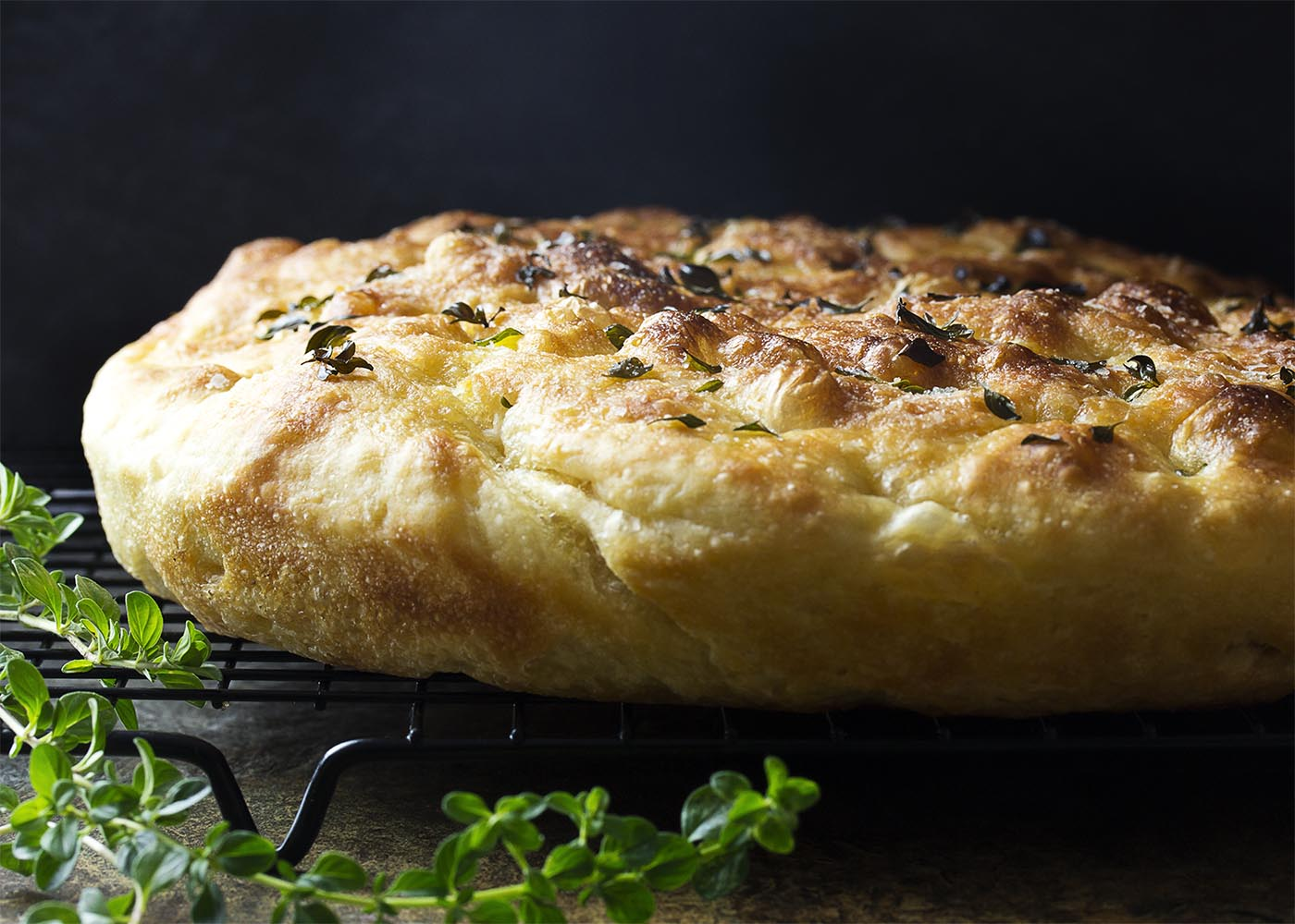 My no-knead focaccia bread with garlic and thyme is made right in a cast iron skillet, giving it a soft and chewy interior and crispy edges. Easy! Great for dinner or for paninis! | justalittlebitofbacon.com