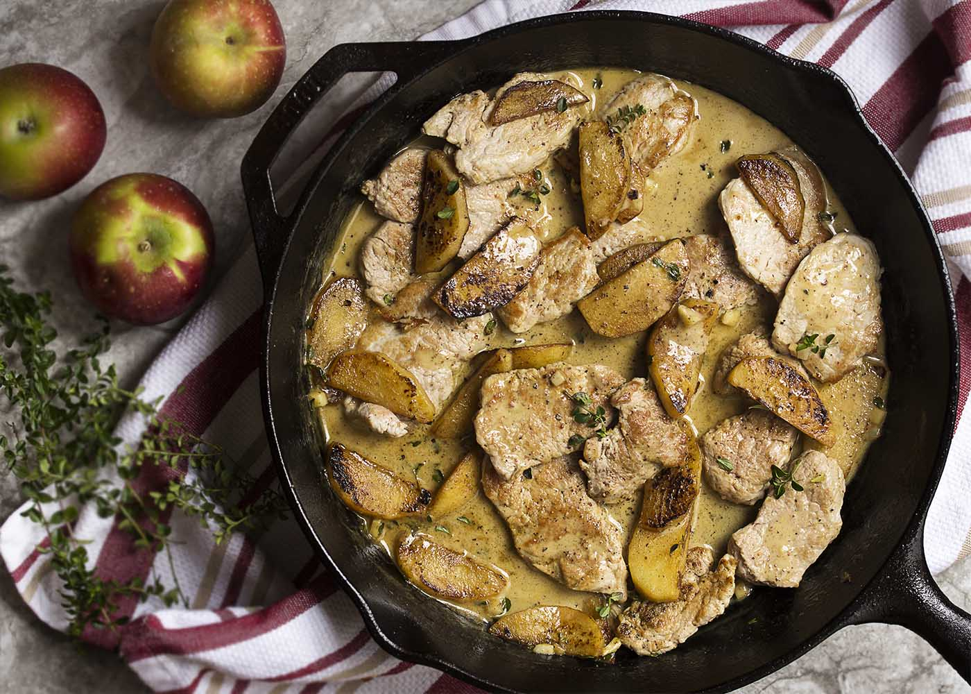 Thin pork tenderloin medallions are quickly pan seared and then tossed with sauteed apples and a cider cream pan sauce in this fall inspired skillet dinner. | justalittlebitofbacon.com