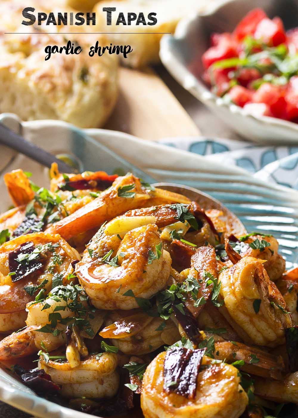 Plump and juicy shrimp, soft sliced garlic, and sweet and smoky paprika combine in this classic tapas recipe for Spanish garlic shrimp. Quick and easy! Make sure you have plenty of bread to soak up the flavorful olive oil!   justalittlebitofbacon.com
