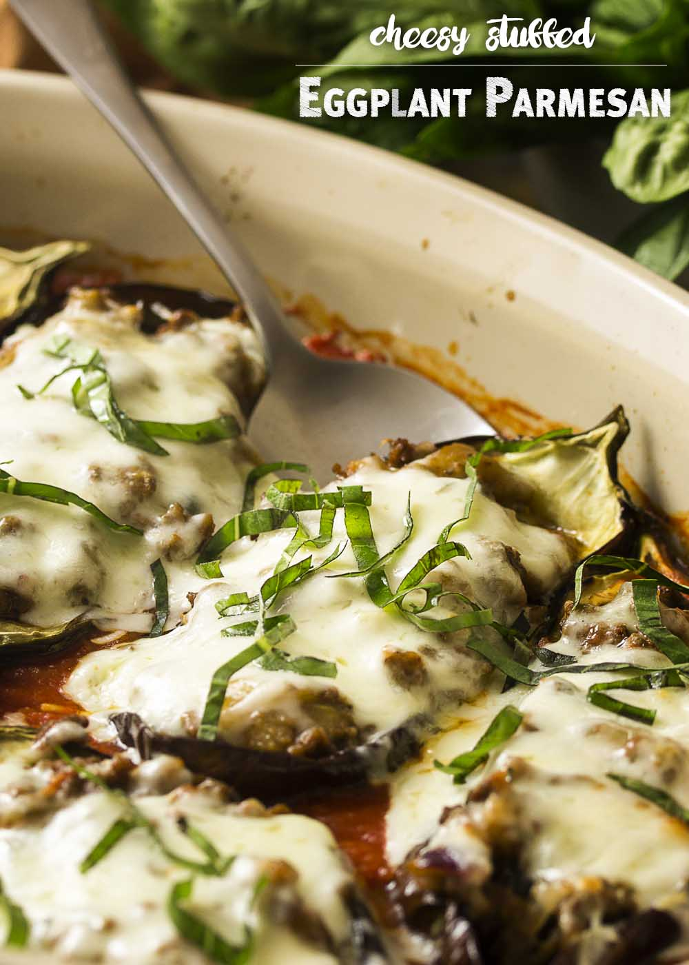 For a fun and tasty way to enjoy eggplant, try stuffed eggplant parmesan! The eggplants are stuffed with ground beef, topped with plenty of mozzarella cheese, and baked in the oven until browned and gooey. Gluten-free. | justalittlebitofbacon.com