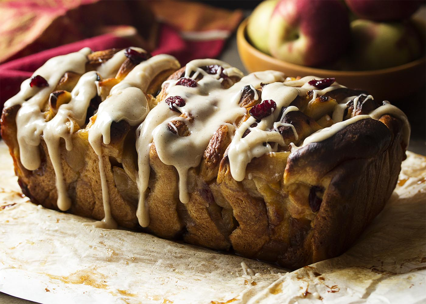 A side view of the finished apple pull apart bread with icing drizzled over the top.