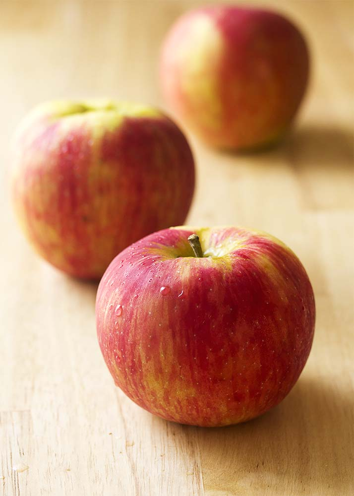 Honeycrisp apples sitting on a wooden board.
