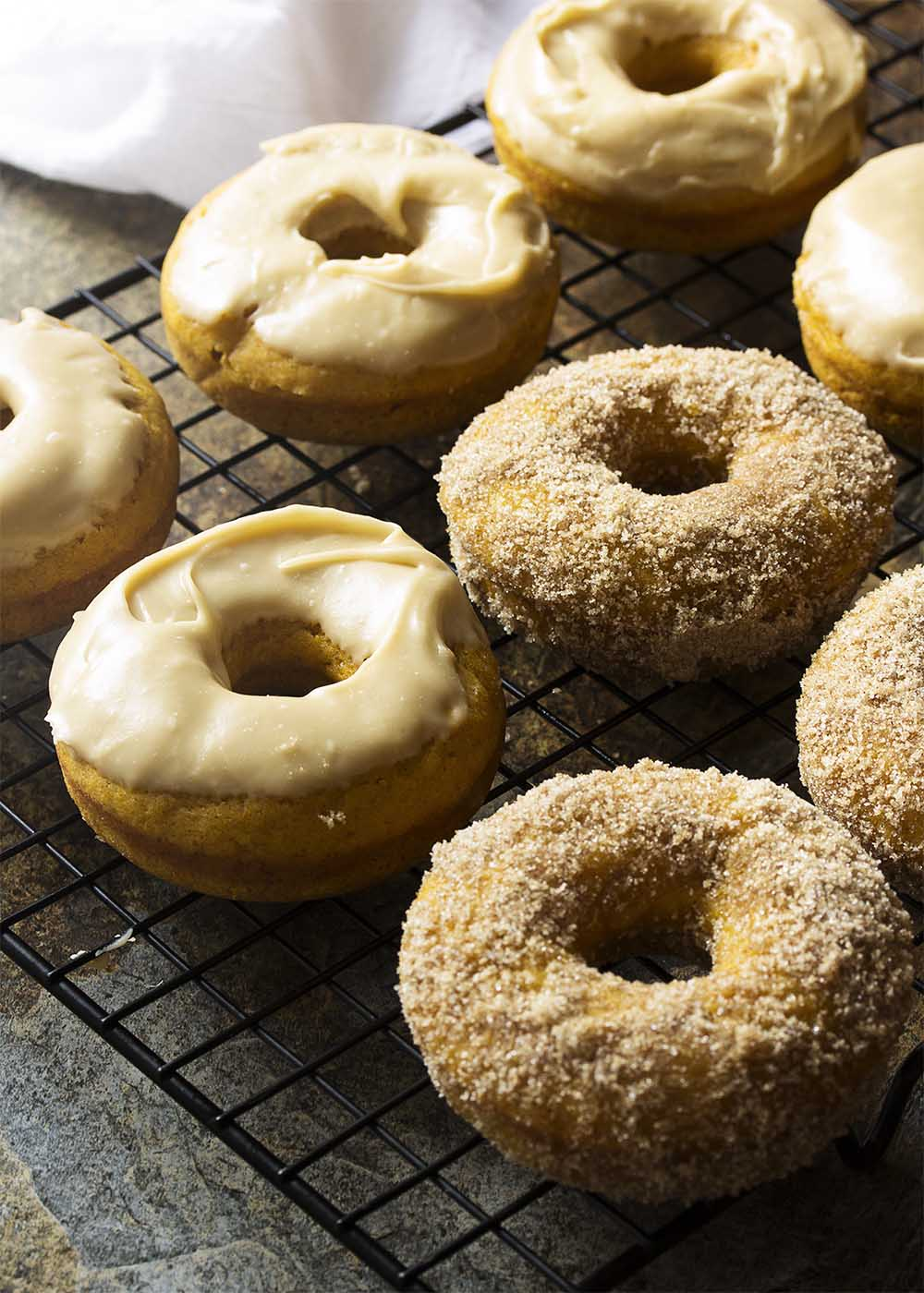 These easy and tasty baked pumpkin donuts are full of pumpkin puree and warming spices for a great fall breakfast or dessert. Either top them with a maple butterscotch glaze or roll them in cinnamon sugar. | justalittlebitofbacon.com