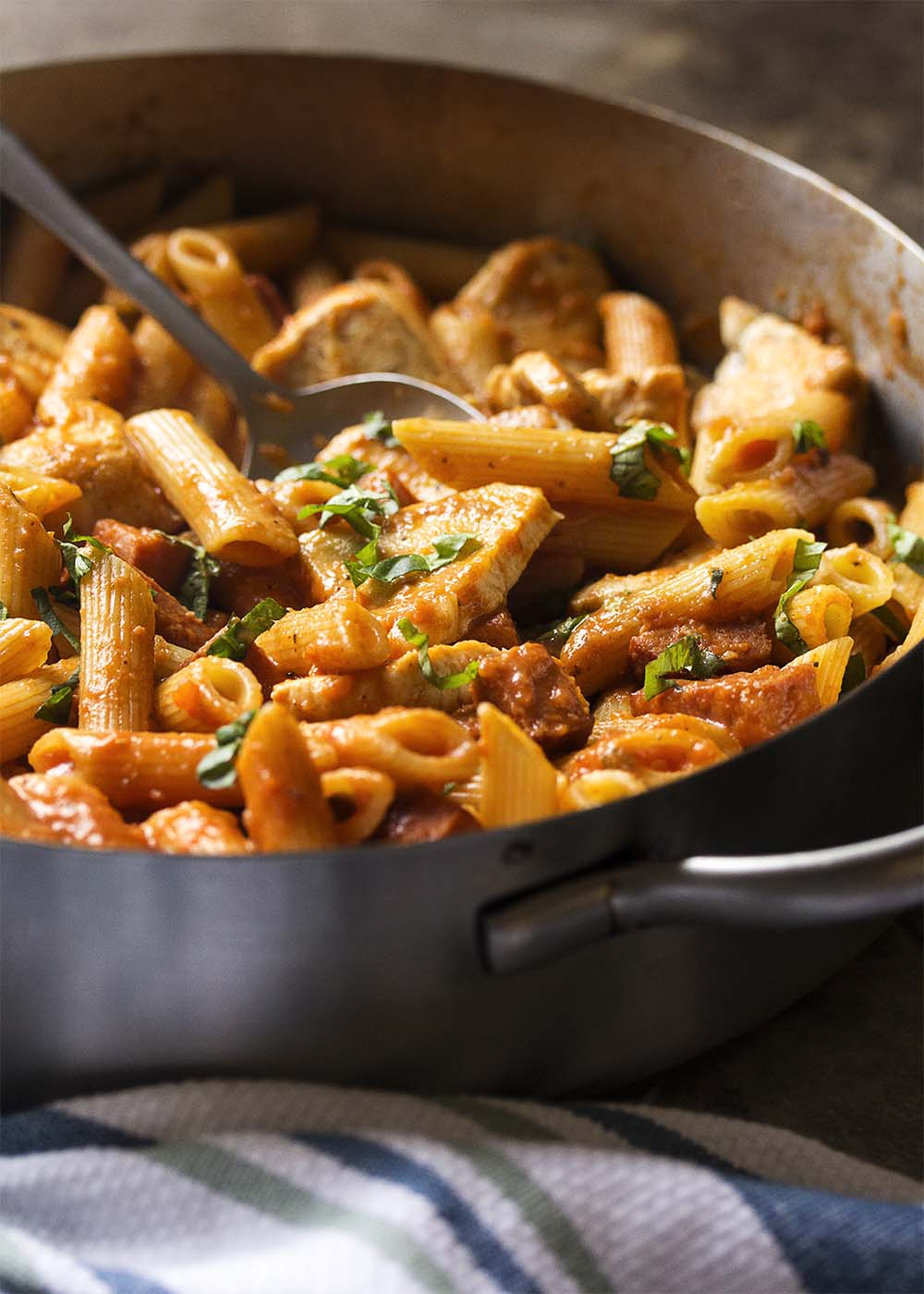 The finished penne alla vodka in the skillet with the chicken and chorizo mixed in and basil sprinkled over the top.